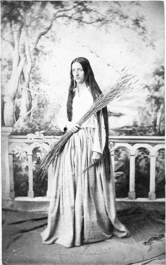 Julia Tredwell in a studio portrait probably taken to commemorate her performance in a tableau or parlor theatrical in which she portrayed the Biblical Ruth. Usually she wore her hair in braids that wound round. . .and round the back of her head.
